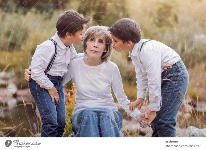 Großmutter mit ihren Enkelkindern, die auf dem Gebiet sitzen Lifestyle Garten Mensch maskulin feminin Weiblicher Senior Frau Geschwister Bruder Großeltern