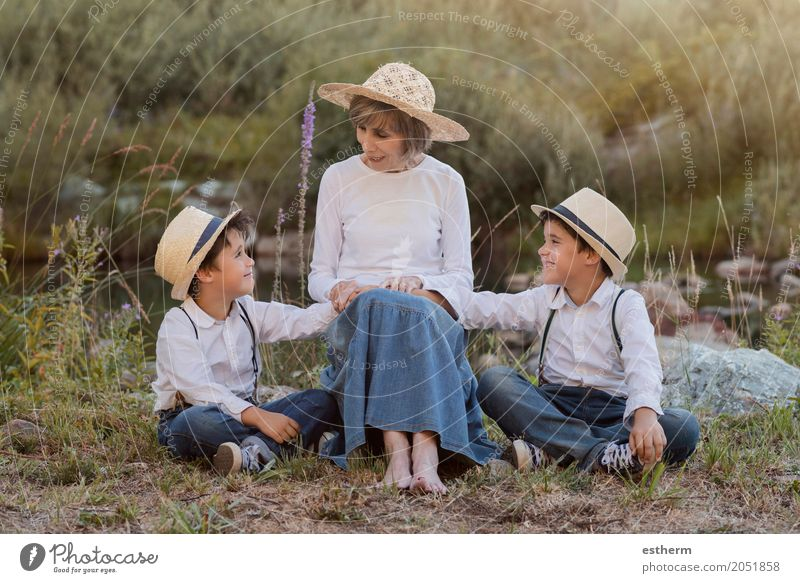 Großmutter mit ihren Enkelkindern, die auf dem Gebiet sitzen Lifestyle Freude Garten Mensch maskulin feminin Kind Kleinkind Junge Geschwister Bruder Großeltern