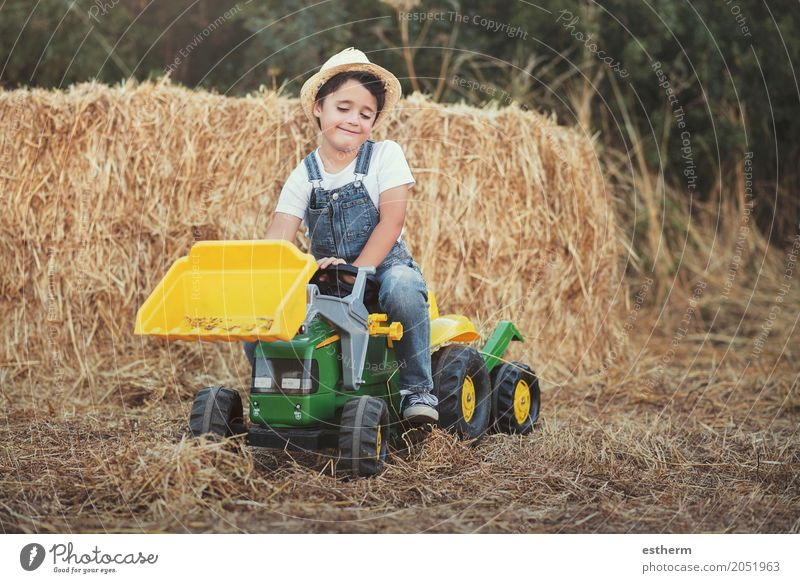 Kind, das mit Spielzeugtraktor auf Wiese spielt Mensch Ferien & Urlaub & Reisen Freude Lifestyle Gefühle Junge lachen Spielen Glück Garten Kindheit sitzen