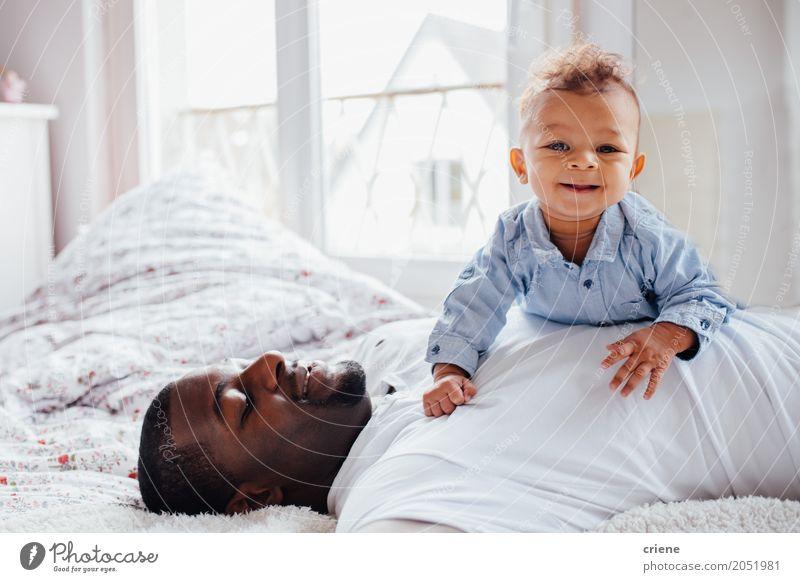 Junger afroamerikanischer Vater und Kleinkind kuscheln zusammen. Lifestyle Freude Glück Schlafzimmer Mensch maskulin Baby Junger Mann Jugendliche Erwachsene