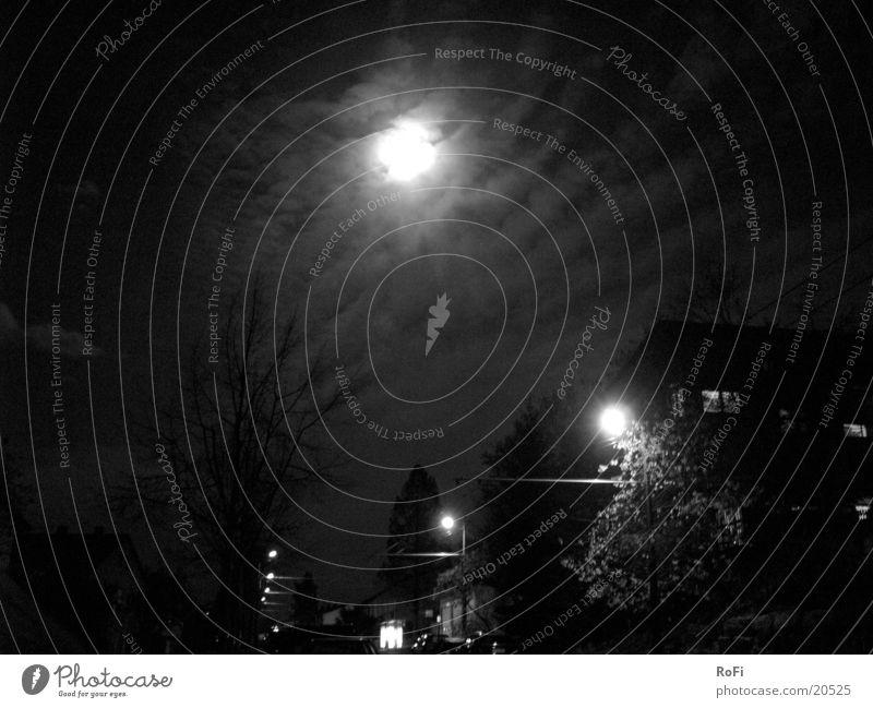 Vollmond über Straßenlampen Straßenbeleuchtung Nacht Wolken dunkel Grauwert Langzeitbelichtung Club Mond Licht Schwarzweißfoto