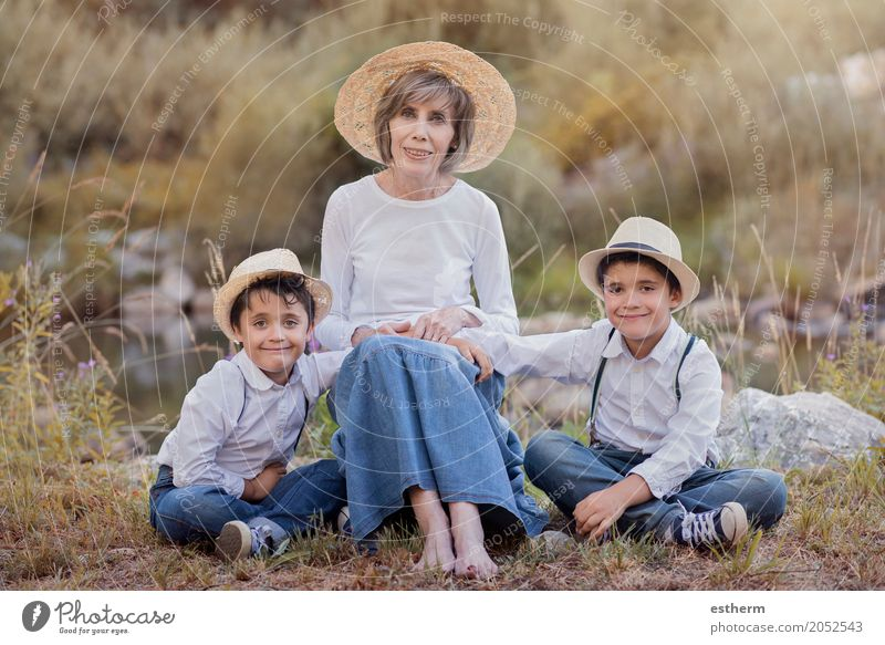 Großmutter mit ihren Enkelkindern, die auf dem Gebiet sitzen Lifestyle Mensch maskulin feminin Kind Kleinkind Junge Weiblicher Senior Frau Geschwister Bruder