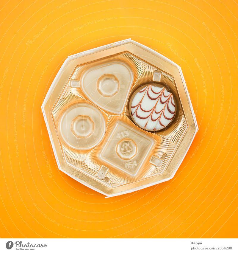 Pralinenschachtel mit einer Praline Lebensmittel Süßwaren Schokolade Konfekt braun gold orange weiß genießen 1 Zucker edel Farbfoto Menschenleer süß gelb Hunger