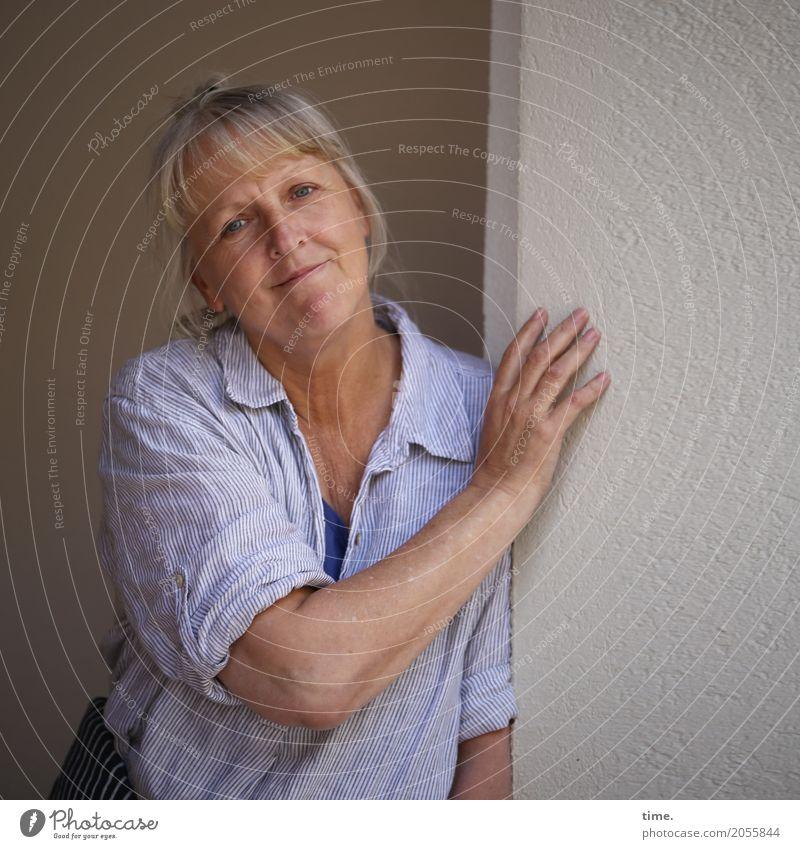 AST 10 | gastfreundlich feminin Frau Erwachsene Mensch Mauer Wand Hemd blond kurzhaarig beobachten festhalten Lächeln Blick warten schön Wärme Zufriedenheit