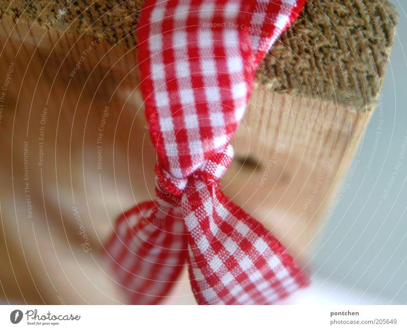 Eine Schleife aus rot-weiß kariertem Stoff befestigt an einem Holzbrett. Geschenkband. Weihnachten. Schenken Zierde verschönern Strukturen & Formen retro