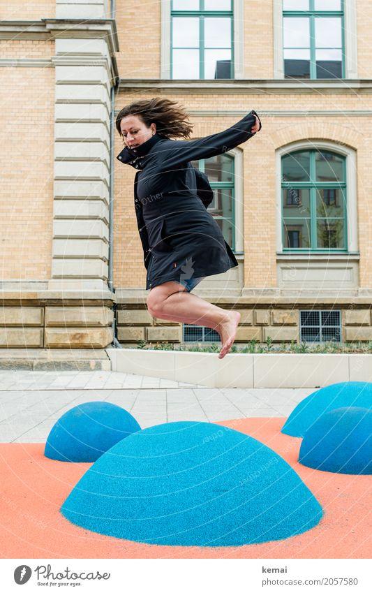 Frau im Mantel springt barfuss auf blauen Gummihügeln Lifestyle Leben Wohlgefühl Zufriedenheit Freizeit & Hobby Spielen Spielplatz Ferien & Urlaub & Reisen