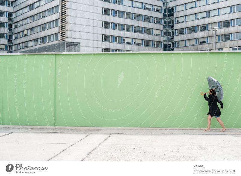 Frau mit Regenschirm vor grüner Wand, im Hintergrund Hochhäuser Stil Freizeit & Hobby Spielen Ausflug Freiheit Städtereise Mauer Mensch feminin Erwachsene Leben