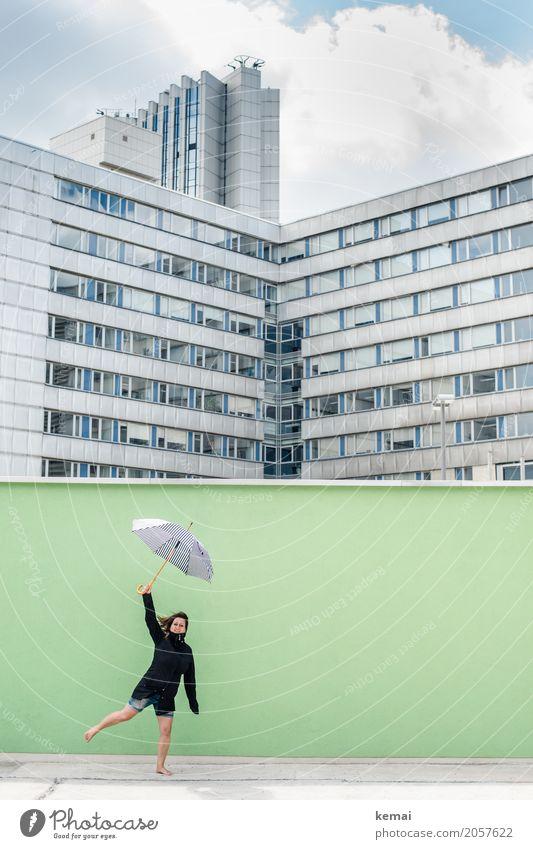 Frau mit Regenschirm vor grüner Wand, im Hintergrund Hochhäuser Lifestyle Leben Wohlgefühl Zufriedenheit Freizeit & Hobby Spielen Ausflug Abenteuer Freiheit