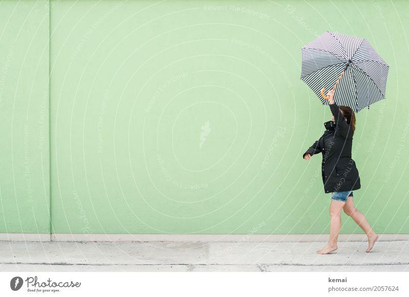 Frau läuft mit Regenschirm vor grüner Wand Lifestyle Stil harmonisch Wohlgefühl Zufriedenheit Freizeit & Hobby Spielen Ausflug Freiheit Mensch feminin