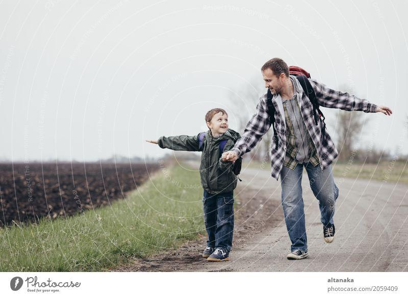 Vater und Sohn gehen zur Tageszeit auf der Straße. Die Menschen haben Spaß im Freien. Konzept der freundlichen Familie. Lifestyle Freude Glück Freizeit & Hobby