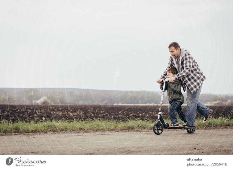 Vater und Sohn, die auf der Straße zur Tageszeit spielen. Lifestyle Freude Glück Freizeit & Hobby Spielen Ferien & Urlaub & Reisen Ausflug Abenteuer Freiheit