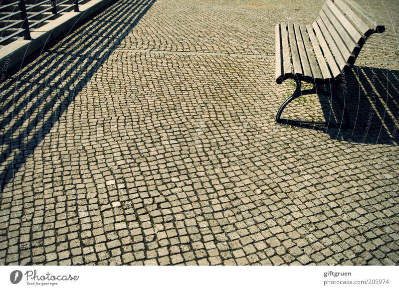 hitzeferien Platz Bank Sitzgelegenheit Parkbank Holzbank Geländer Kopfsteinpflaster Schattenspiel Fluchtlinie leer Sommer Schönes Wetter frei Straßenbelag Möbel