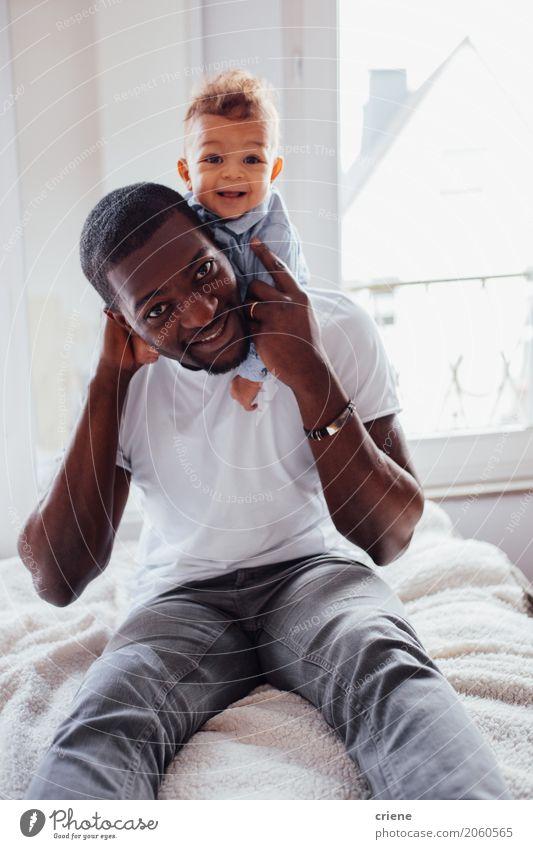 Portrait des afrikanischen Vater- und Kleinkindsohns Lifestyle Freude Häusliches Leben Schlafzimmer maskulin Baby Junge Junger Mann Jugendliche Erwachsene