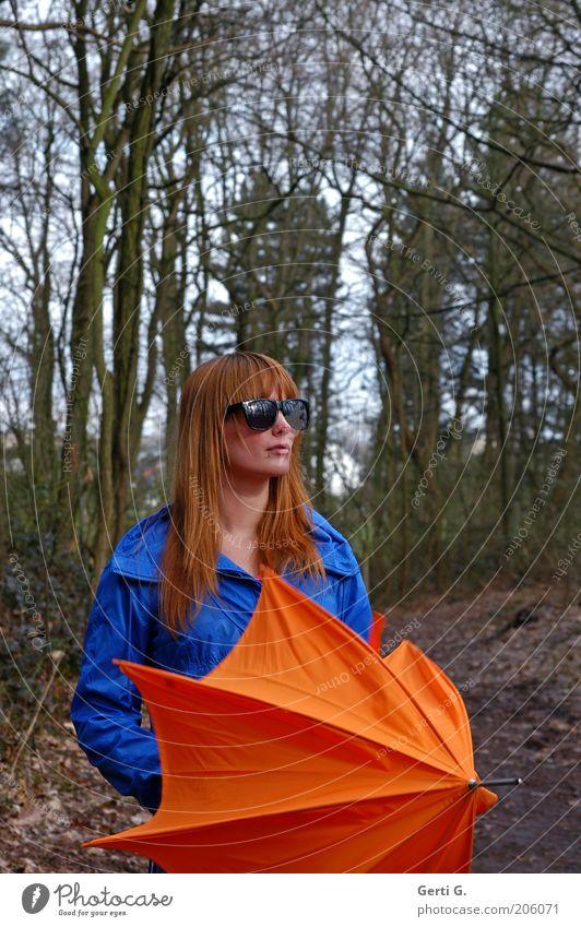 rothaariger hübscher Teenager, langhaarig mit schwarzer Sonnenbrille, blauer Jacke, orangefarbenem Schirm im Wald Frau besonnen bedächtig schön Regenschirm