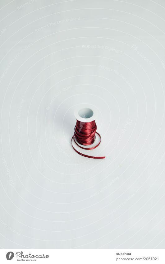 die rote schnur Geschenkband verschönern schleifen machen geschenke einbinden Schnur abgerollt Vor hellem Hintergrund Hintergrund neutral Rolle