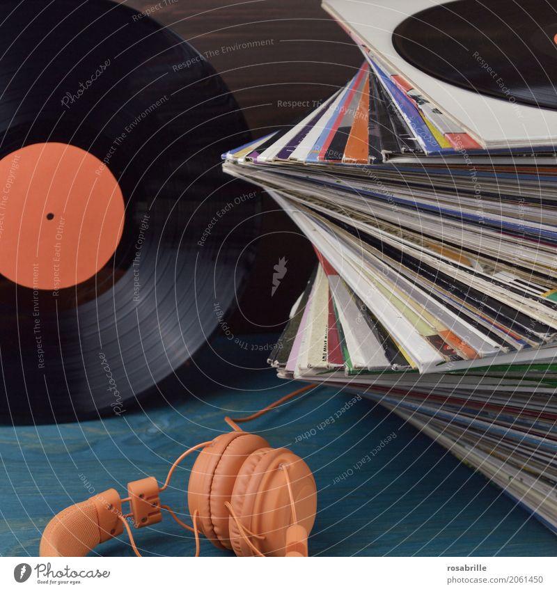 good old music - ein Stapel Schallplattenhüllen, eine Vinyl-LP mit orangenem leeren Etikett und ein orangener Kopfhörer auf blauem Holzuntergrund und brauner Rückwand