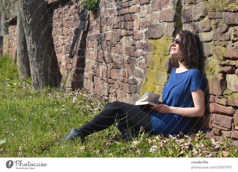 Sonne tanken - junge brünette Frau sitzt in einem Park im Gras an eine Steinmauer gelehnt mit einem Buch in der Hand und genießt die Sonne Mensch feminin