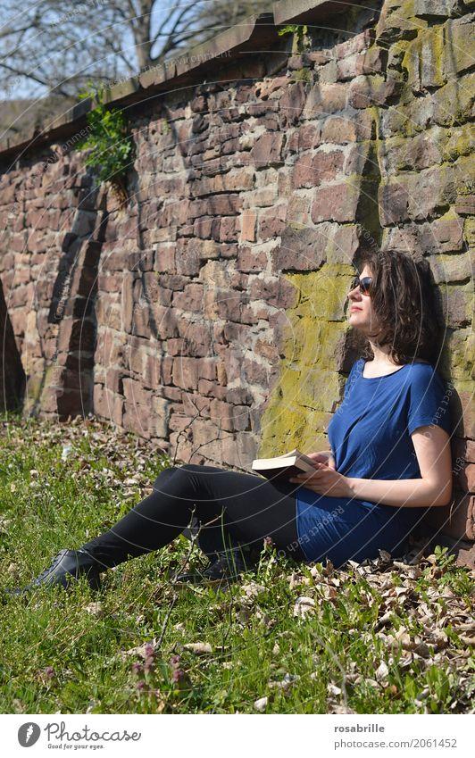 Sonne tanken - junge brünette Frau sitzt in einem Park im Gras an eine Steinmauer gelehnt mit einem Buch in der Hand und genießt die Sonne Wohlgefühl