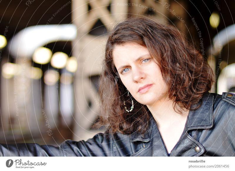 coole junge Frau mit schwarzer Lederjacke steht vor Stahlträgern in einer Unterführung und schaut selbstbewusst in die Kamera Mensch feminin Junge Frau