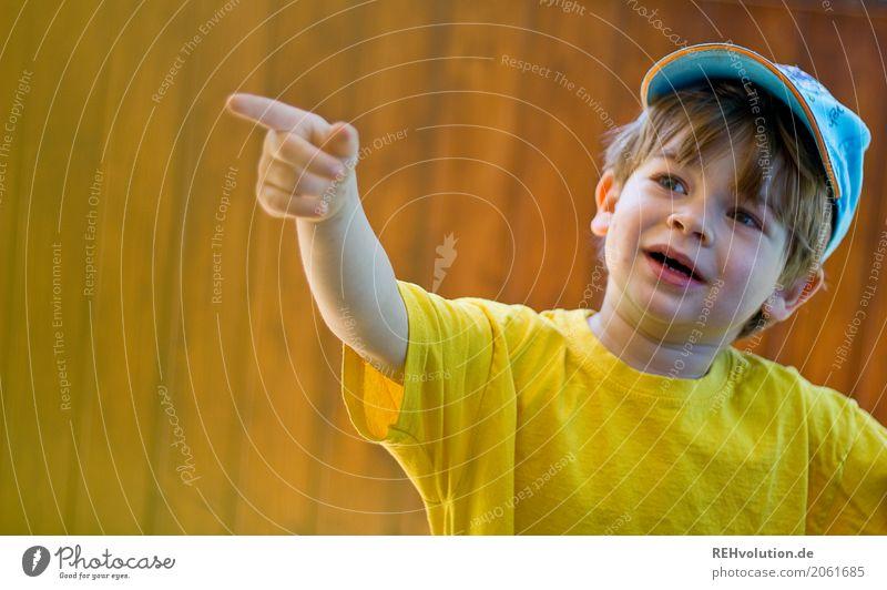 Kind zeigt auf etwas Mensch Kleinkind Junge Kindheit Gesicht 1 1-3 Jahre Sommer T-Shirt Mütze Holz Lächeln sprechen authentisch klein natürlich niedlich gelb
