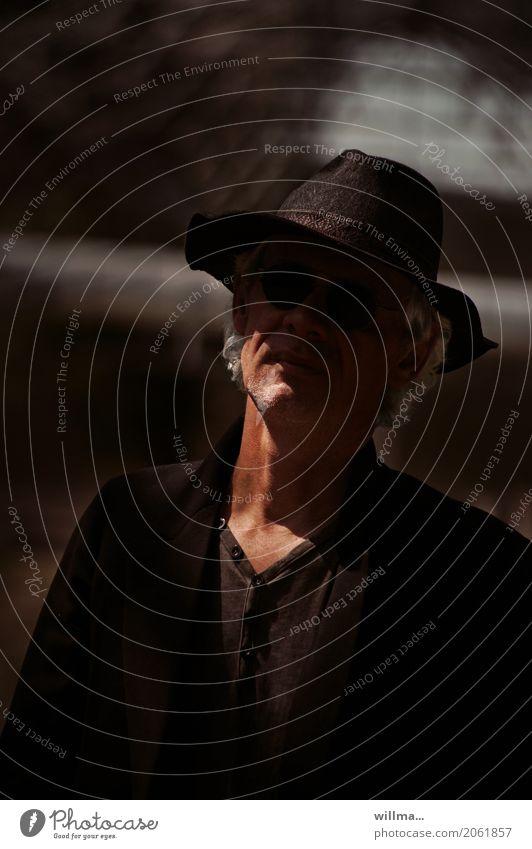 Ein Mann hat viel erlebt Schlapphut weißhaarig interessant schwarz schwarz gekleidet Leben 45-60 Jahre Hut Sonnenbrille Locken Dreitagebart dunkel Coolness