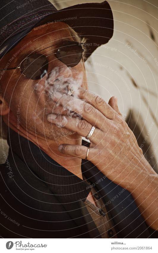 Rauchender Mann mit Schlapphut und dunkler Sonnnenbrille Sonnenbrille Frack weißhaarig Dreitagebart Coolness Bartstoppel Schoßrock Hut Ring lässig rauchend