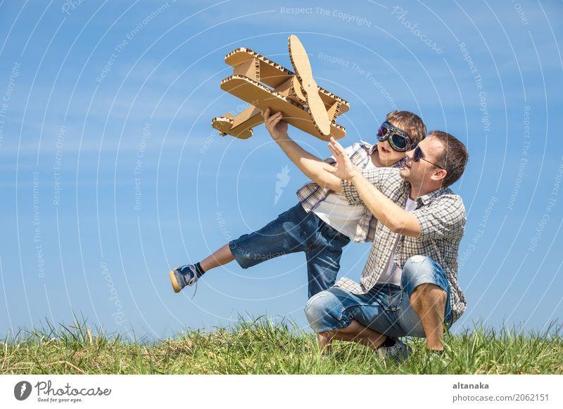 Vater und Sohn, die mit Pappspielzeugflugzeug spielen Lifestyle Freude Glück Leben Freizeit & Hobby Spielen Ferien & Urlaub & Reisen Abenteuer Freiheit Sommer