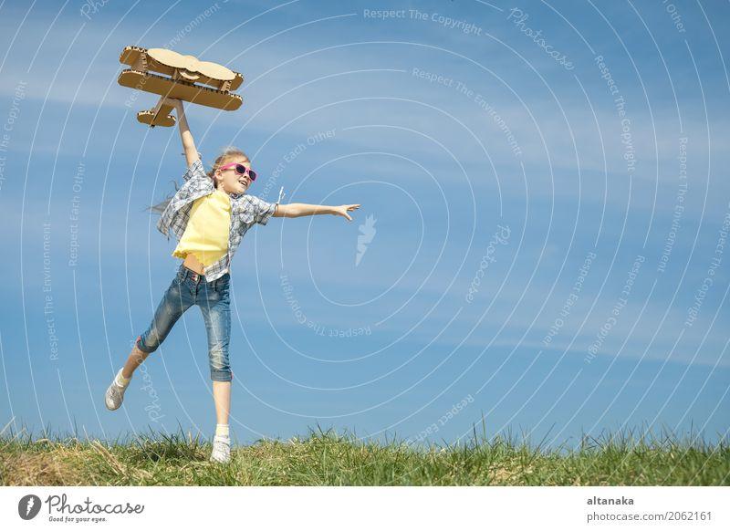 Kleines Mädchen, das mit Pappspielzeugflugzeug spielt Mensch Kind Himmel Natur Ferien & Urlaub & Reisen Sommer Sonne Freude Lifestyle Sport Gras Spielen klein