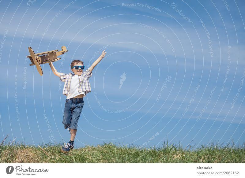 Kleiner Junge, der mit Pappspielzeugflugzeug spielt Lifestyle Freude Glück Spielen Ferien & Urlaub & Reisen Abenteuer Freiheit Sommer Sonne Sport Erfolg Kind