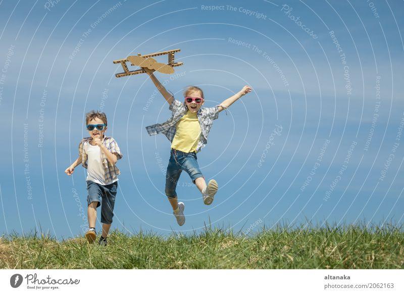 Zwei Kleinkinder, die mit Pappspielzeugflugzeug spielen Mensch Kind Natur Ferien & Urlaub & Reisen Sommer Sonne Freude Lifestyle Gefühle Sport Gras Junge