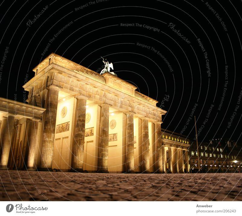 Brandenburger Tor in Berlin bei Nacht schön Stadt Pflanze schwarz gelb Berlin Gebäude Stimmung Beleuchtung Architektur Deutschland Europa ästhetisch Zeichen Bauwerk Kopfsteinpflaster
