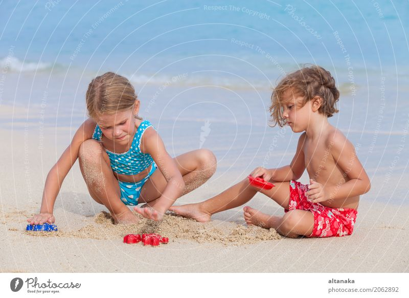 Zwei glückliche Kinder, die auf dem Strand spielen Mensch Natur Ferien & Urlaub & Reisen Sommer schön Sonne Hand Meer Erholung Freude Lifestyle Gefühle