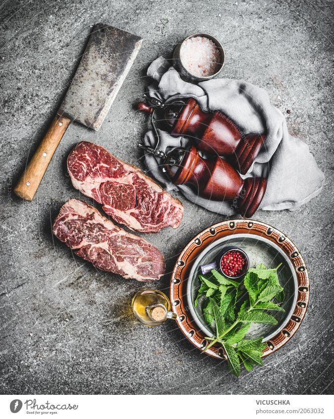 Marmorierte Ribeye Steaks auf dem Küchentisch Lebensmittel Fleisch Kräuter & Gewürze Ernährung Mittagessen Abendessen Bioprodukte Geschirr Messer Stil Design