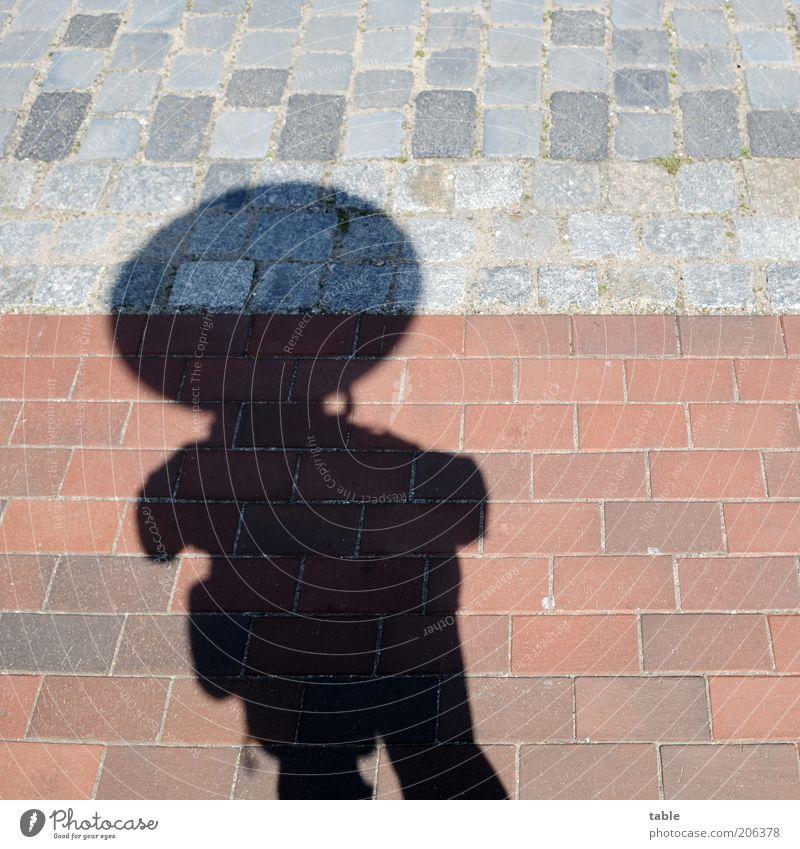 hombre emprendedor Mensch Mann rot schwarz Erwachsene dunkel grau Stein warten maskulin groß stehen rund Symbole & Metaphern Backstein Bürgersteig