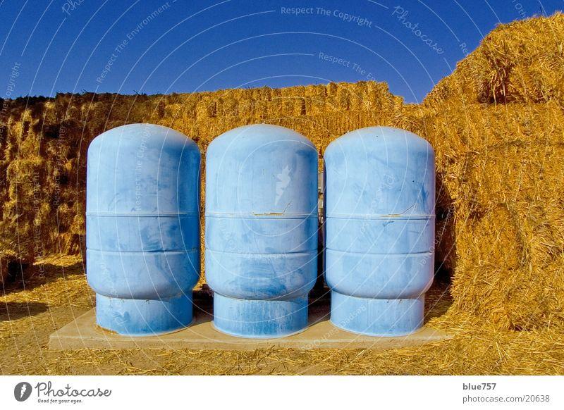 Drei blaue Behälter Himmel gelb obskur Stroh Behälter u. Gefäße