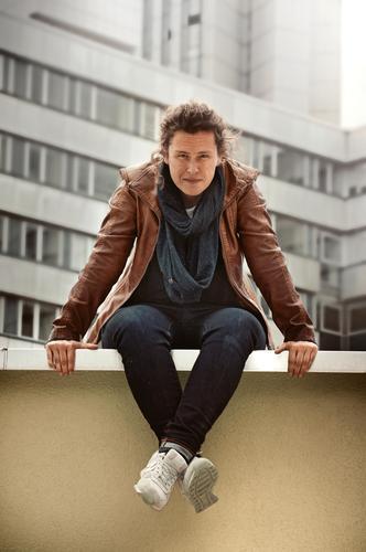 jugendliche sitzt auf einer mauer in der stadt Mensch Junge Frau Jugendliche Erwachsene 1 Chemnitz Bürogebäude Mauer Wand Lederjacke Jeanshose Schal brünett