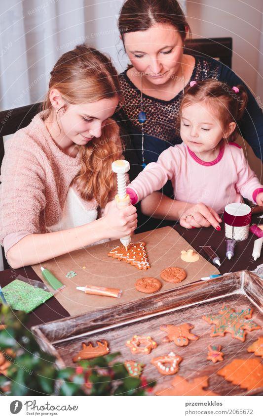 Familie schmückt gebackene Weihnachts-Lebkuchen mit Zuckerguss Dekoration & Verzierung Tisch Küche Feste & Feiern Kind Mensch Frau Erwachsene