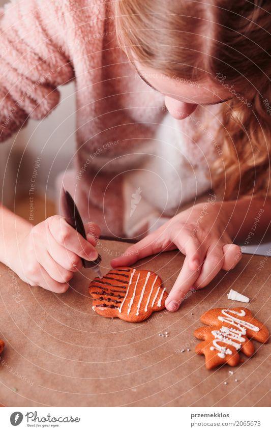 Mädchen, das Weihnachtslebkuchenplätzchen mit Schokolade verziert Mensch Jugendliche Weihnachten & Advent Lifestyle Feste & Feiern Dekoration & Verzierung
