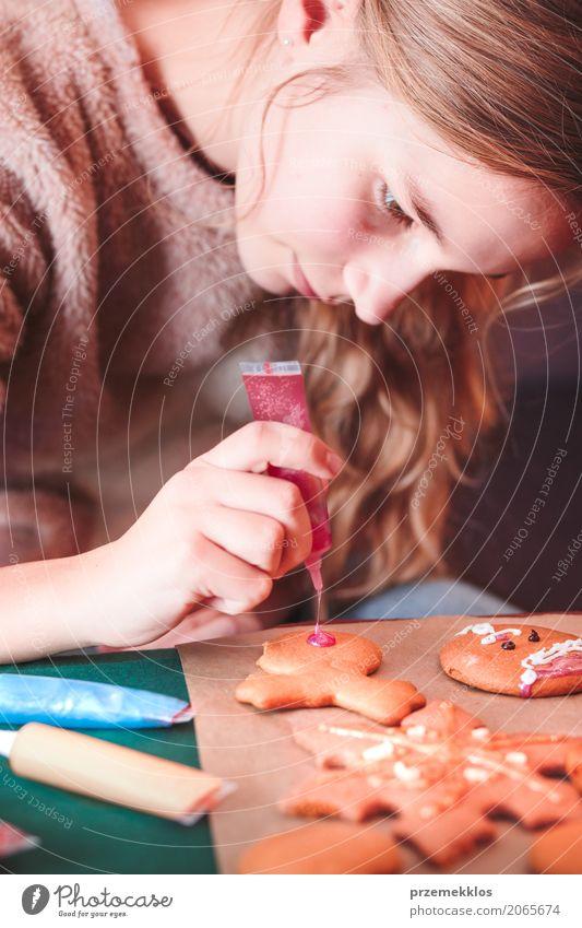Mädchen, das Weihnachtslebkuchenplätzchen mit dem Zuckerguss verziert Lifestyle Dekoration & Verzierung Tisch Feste & Feiern Weihnachten & Advent Mensch 1