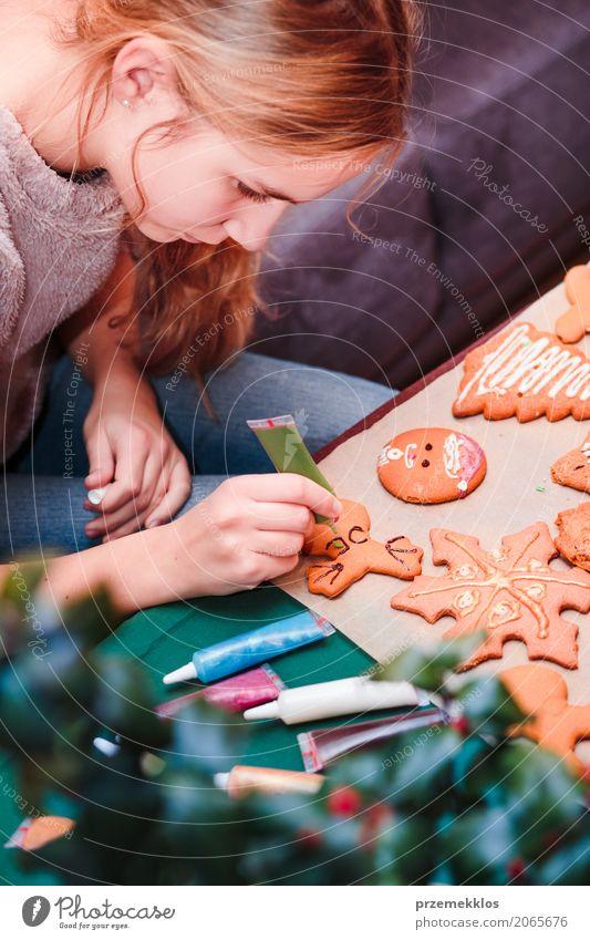 Mädchen, das Weihnachtslebkuchenplätzchen mit Schokolade verziert Lebensmittel Lifestyle Dekoration & Verzierung Tisch Feste & Feiern Weihnachten & Advent