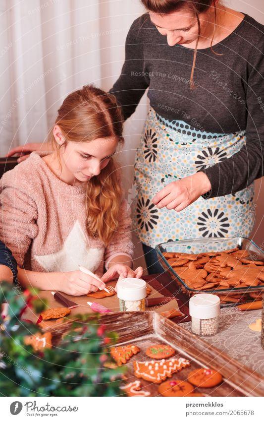 Mädchen, das Weihnachtslebkuchenplätzchen mit dem Zuckerguss verziert Mensch Kind Frau Weihnachten & Advent Erwachsene Lifestyle Dekoration & Verzierung