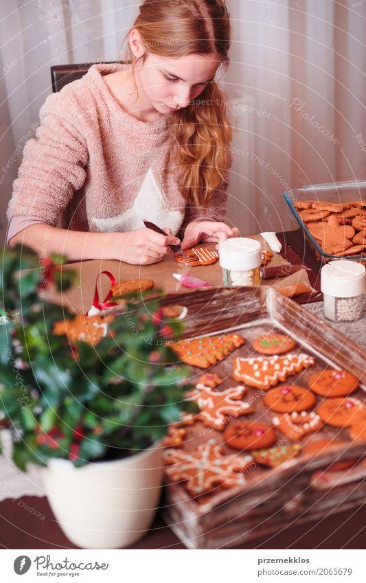 Mädchen, das Weihnachtslebkuchenplätzchen mit dem Zuckerguss verziert Mensch Kind Lifestyle Feste & Feiern Dekoration & Verzierung Kindheit Tisch Küche