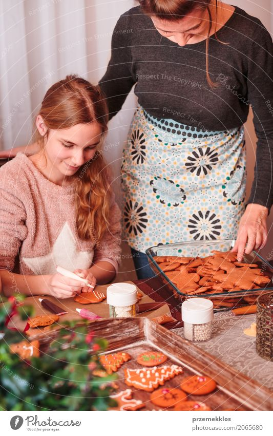 Mädchen, das Weihnachtslebkuchenplätzchen mit dem Zuckerguss verziert Mensch Kind Frau Erwachsene Familie & Verwandtschaft Feste & Feiern
