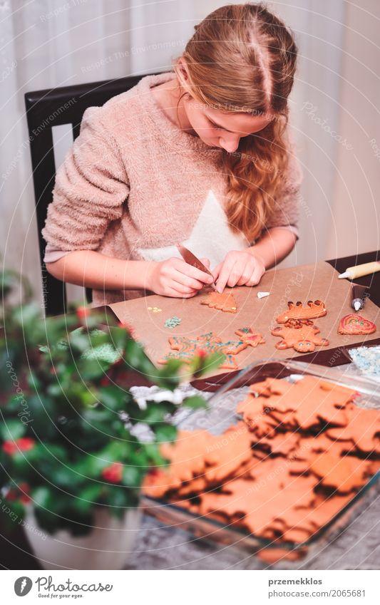 Mädchen, das Weihnachtslebkuchenplätzchen mit Schokolade verziert Lifestyle Dekoration & Verzierung Tisch Küche Feste & Feiern Weihnachten & Advent Mensch 1