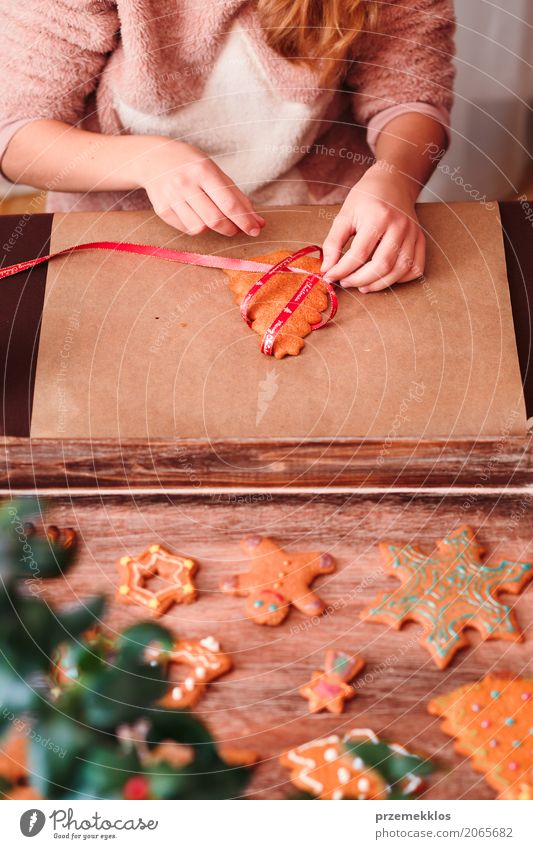 Mädchen, das gebackene Weihnachtslebkuchenplätzchen mit Band bindet Lifestyle Dekoration & Verzierung Tisch Feste & Feiern Weihnachten & Advent Handwerk Mensch
