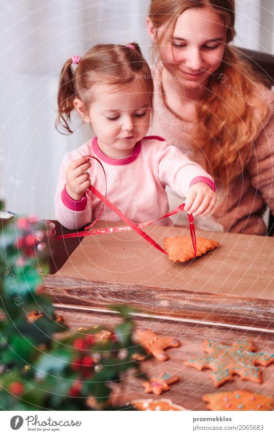 Mädchen, die gebackene Weihnachtslebkuchenplätzchen mit Band binden Mensch Kind Jugendliche Lifestyle Familie & Verwandtschaft Feste & Feiern