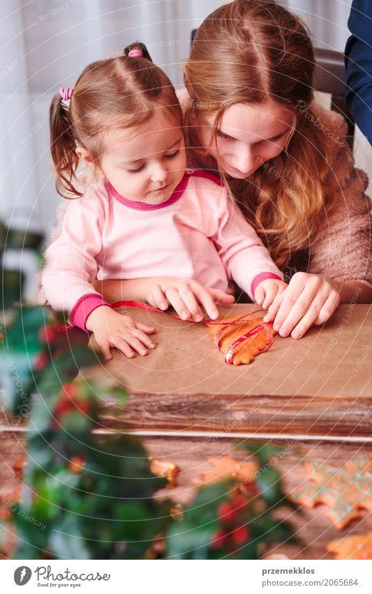 Mädchen, die gebackene Weihnachtslebkuchenplätzchen mit Band binden Mensch Kind Frau Weihnachten & Advent Erwachsene Lifestyle Familie & Verwandtschaft