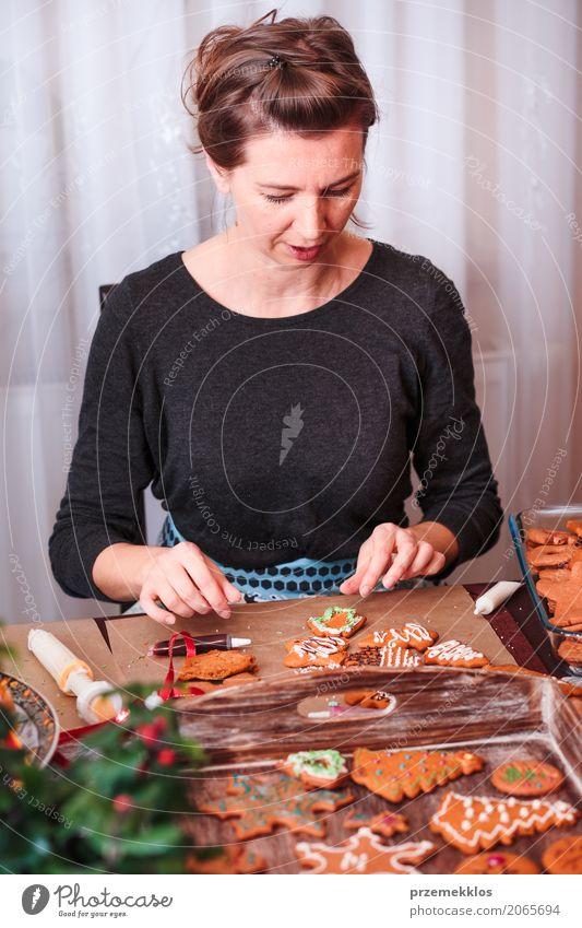 Frau, die gebackene Weihnachtslebkuchen mit dem Bereifen verziert Mensch Weihnachten & Advent Erwachsene Lifestyle Feste & Feiern Dekoration & Verzierung Tisch