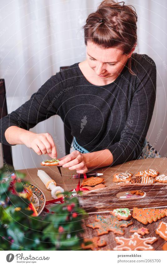 Frau, die gebackenen Weihnachtslebkuchen mit dem Bereifen verziert Mensch Weihnachten & Advent Erwachsene Lebensmittel Feste & Feiern Dekoration & Verzierung