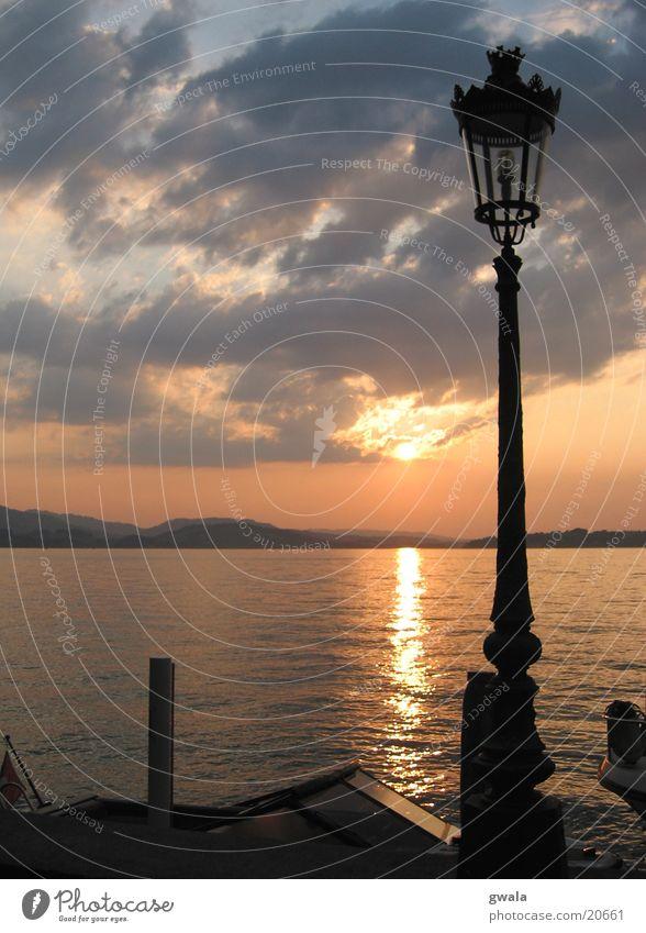 sunsetlaterne Farbfoto Außenaufnahme Menschenleer Dämmerung Silhouette Sonnenlicht Gegenlicht Wellen Wasser Wolken Sonnenaufgang Sonnenuntergang Seeufer